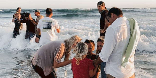 People get baptized at the Saturate OC event July 10, on Huntington Beach, Calif.
