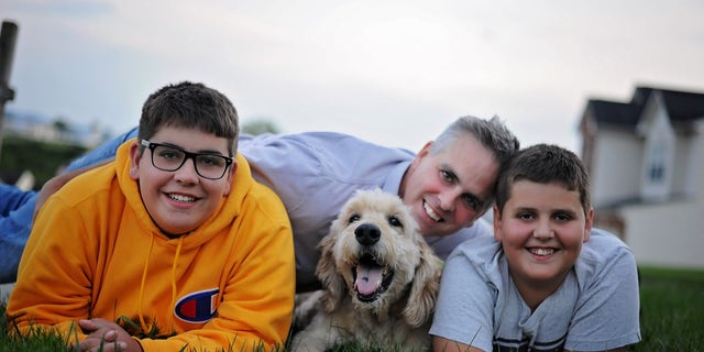 Jason Wright and his sons posing with family dog Pilgrim in last photoshoot before he passed