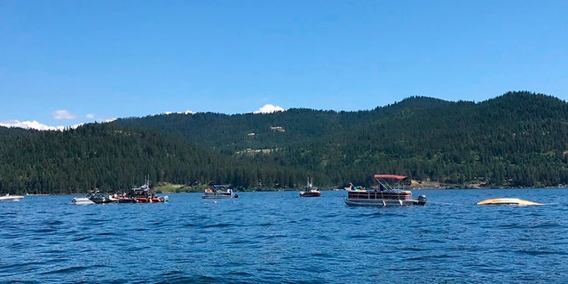 Boaters flag down authorities to a crashed seaplane near Powderhorn Bay on Lake Coeur d'Alene on Sunday, July 5, 2020, south of Coeur d'Alene, Idaho. (Stephanie Hammett/The Spokesman-Review via AP)