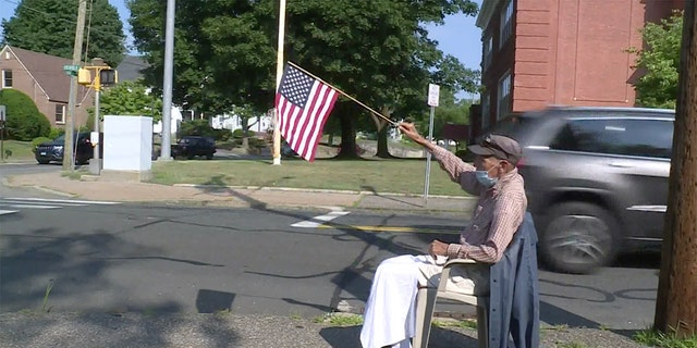John Mastrocola, a 95-year-old World War II veteran, grabs his cane, a chair and an American flag every day at 8 a.m. and goes out to sit beside the sidewalk to wish his community a patriotic good morning. (Courtesy FOX61)