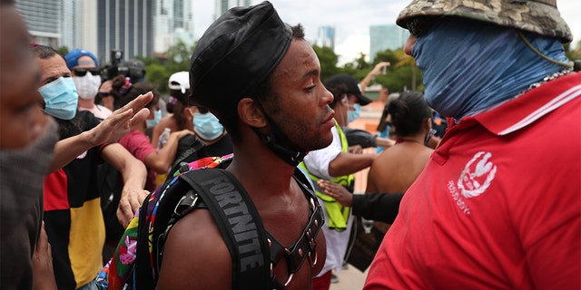 Jonathan Gartrelle (L), participating in a protest against police brutality, confronts a demonstrator taking part in a counter demonstration on June 14, in Miami. (Photo by Joe Raedle/Getty Images)