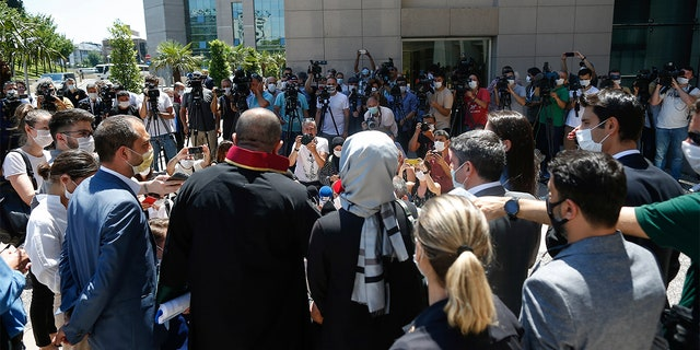 Hatice Cengiz, centre back to camera, the fiancee of slain Saudi journalist Jamal Kashoggi, talks to members of the media outside a court in Istanbul, Friday, July 3, 2020.