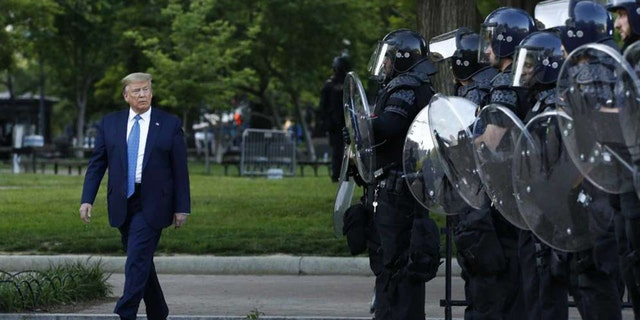 In this Monday, June 1, 2020, file photo President Donald Trump walks past police in Lafayette Park after visiting outside St. John's Church across from the White House in Washington.