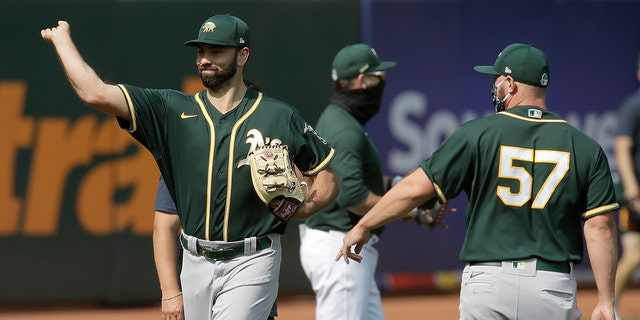Oakland Athletics pitcher Lou Trivino, left, warms up during baseball practice Wednesday, July 15, 2020, in Oakland, Calif. (AP Photo/Ben Margot)