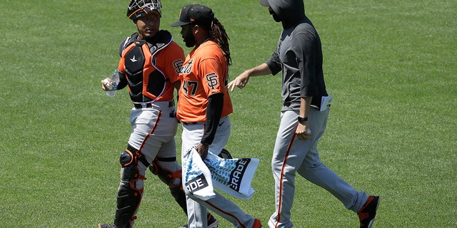 San Francisco Giants' Chadwick Tromp, left, walks with Johnny Cueto, center, and another player during baseball practice in San Francisco, Tuesday, July 14, 2020. (AP Photo/Jeff Chiu)