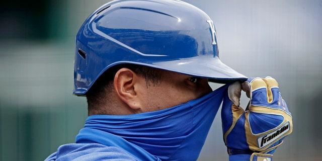 Kansas City Royals' Salvador Perez adjusts his mask during baseball practice at Kauffman Stadium, Thursday, July 16, 2020, in Kansas City, Mo. (AP Photo/Charlie Riedel)