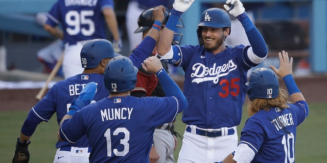 Los Angeles Dodgers' Cody Bellinger (35) is met at home plate after hitting a grand slam during the first inning of an exhibition baseball game against the Arizona Diamondbacks Sunday, July 19, 2020, in Los Angeles. (AP Photo/Marcio Jose Sanchez)