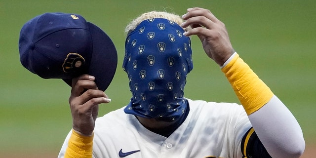 Milwaukee Brewers' Orlando Arcia covers his face with his mask during an intrasquad game Tuesday, July 14, 2020, at Miller Park in Milwaukee. (AP Photo/Morry Gash)