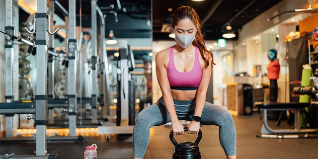 A female athlete is wearing a protective face mask and lifting a kettlebell in a gym. (Stock image)