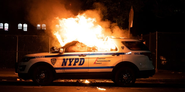 An NYPD police car is set on fire as protesters clash with police during a march against the death in Minneapolis police custody of George Floyd, in the Brooklyn borough of New York City, U.S., May 30, 2020. (REUTERS/Jeenah Moon)