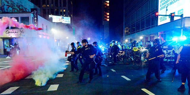 Smoke rises around police as they spray pepper spray during clashes with protesters after a May 31 demonstration over the death of George Floyd, an unarmed black man who died in Minneapolis Police custody, in Boston. A Boston-area man was federally charged Thursday with shooting at a group of police officers after a protest against police brutality.  (Photo by Joseph Prezioso / AFP) (Photo by JOSEPH PREZIOSO/AFP via Getty Images)