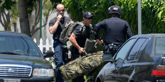 LAPD and SWAT sniper units surround a house where a man armed with a rifle barricaded himself, in Los Angeles in 2014. A former SWAT member filed a lawsuit Tuesday alleging a group of officers encouraged the use of deadly force and engaged in police misconduct.