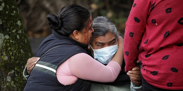 The relatives of a woman killed during the assassination attempt of Mexico City's Chief of Police Omar Garcia Harfuch react near the crime scene on June 26.