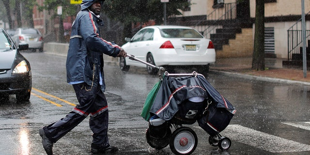 A United States Postal Service (USPS) mail carrier walks through heavy rain as Tropical Storm Fay sweeps across the heavily populated northeastern United States in Jersey City, New Jersey, U.S., July 10.
