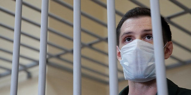 Former U.S. Marine Trevor Reed, who was detained in 2019 and accused of assaulting police officers, stands inside a defendants' cage during a court hearing in Moscow, Russia July 30. (Reuters/Maxim Shemetov)