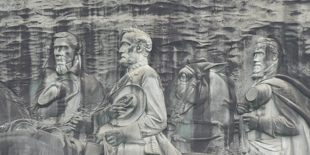 The carving depicts three Confederate figures, Jefferson Davis, Robert E. Lee, and Stonewall Jackson.
