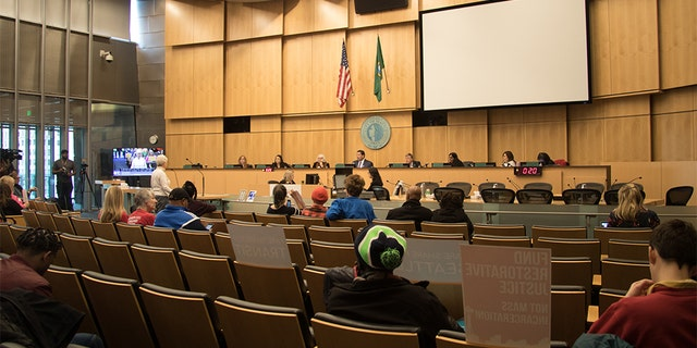 The Seattle City council conducts a meeting in its chambers. Several council members have seen offensive messages written outside their homes in response to their position on defunding the city's police department.