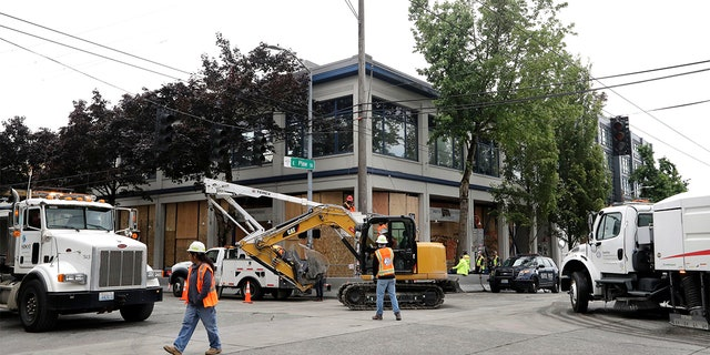 Heavy equipment and a street sweeper roll past a Seattle police precinct being cleaned Wednesday, July 1, 2020, in Seattle, where streets had been blocked off in an area demonstrators had occupied for weeks.