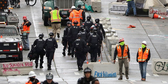 Police and city workers fill a street occupied hours earlier by an encampment of protesters Wednesday, July 1, 2020, in Seattle, where streets had been blocked off in an area demonstrators had occupied for weeks.