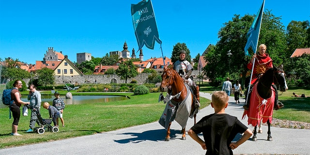 Thomas Lindgren (L) on the horse Soprano and Anders Mansson on Sara, both from the knight society Tornamenteum, patrol the city of Visby on the Swedish island of Gotland on July 23, 2020. (SOREN ANDERSSON/TT News Agency/AFP via Getty Images)