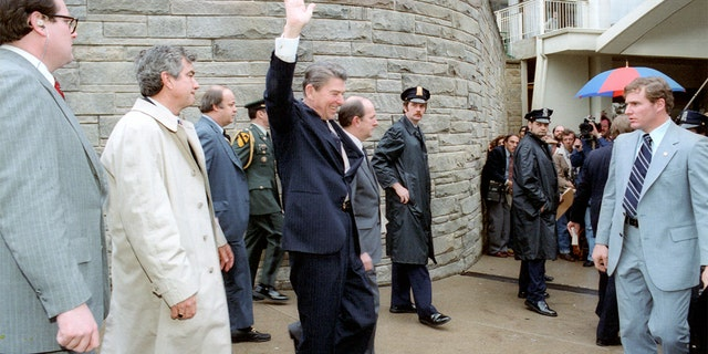 Ronald Reagan waves just moments before he was shot on March 30, 1981. Secret Service Tim McCarthy is on the right in the photo, wearing a business suit and striped tie.