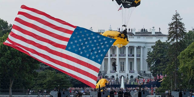 "President Donald Trump and first lady Melania Trump watch as the U.S. Army Golden Knights Parachute Team descend during a ""Salute to America"" event on the South Lawn of the White House, Saturday, July 4, 2020, in Washington. (AP Photo/Alex Brandon)"