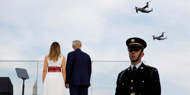 "President Donald Trump and first lady Melania Trump watch as V-22 Osprey aircraft perform a flyover during a ""Salute to America"" event on the South Lawn of the White House, Saturday, July 4, 2020, in Washington. (AP Photo/Patrick Semansky)"