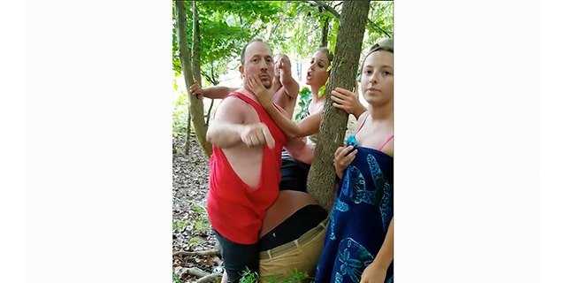 """In this July 4, 2020, image taken from video provided by Brennan Golightly, a group of people surround Vauhxx Booker, center, as he is bent over leaning against a tree, at Monroe Lake near Bloomington, Ind. Two men are facing charges after Booker said a group of white men assaulted him in Indiana and threatened to """"get a noose"""" after claiming that he and his friends had trespassed on private property. Monroe County prosecutors on Friday, July 17, 2020, charged Sean Purdy, left, with felonies of criminal confinement, battery resulting in moderate bodily injury and intimidation."""