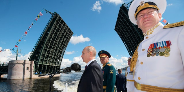 President Vladimir Putin, left, Admiral Nikolai Yevmenov, Commander-in-Chief of the Russian Navy, right, and Russian Defence Minister Sergei Shoigu inspect warships during the Navy Day parade in St.Petersburg, Russia, on Sunday, July 26, 2020. (Alexei Druzhinin, Sputnik, Kremlin Pool Photo via AP)