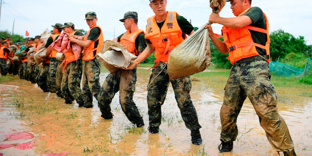 In this photo released by Xinhua News Agency, Chinese paramilitary policemen form a line to move sandbags to reinforce a dike along the banks of Poyang Lake in Poyang County in eastern China's Jiangxi Province, July 12.