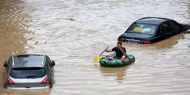 In this photo released by Xinhua News Agency, a man paddles with an inflatable boat past submerged cars during a flood in Rongshui County in southern China's Guangxi Zhuang Autonomous Region, July 11.