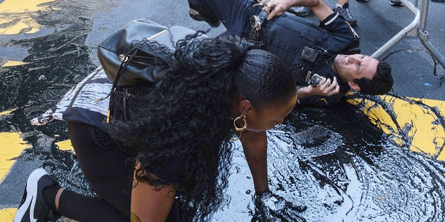 An NYPD officer slips and falls during an attempt to detain a protester pouring black paint on the Black Lives Matter mural outside of Trump Tower on Fifth Avenue in the Manhattan borough of New York on Saturday. (AP Photo/Yuki Iwamura)