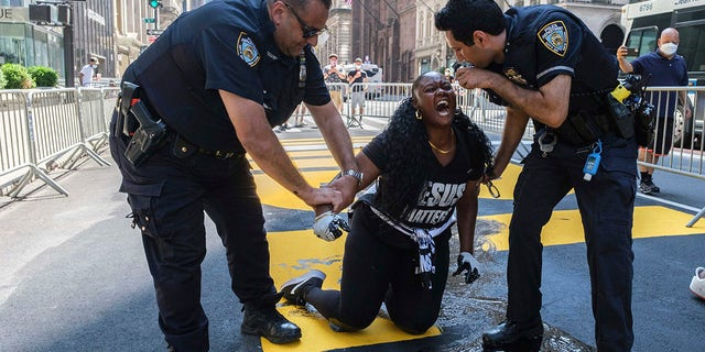 New York Police Department officers attempt to detain a protester who they say used black paint to defacethe Black Lives Matter mural outside of Trump Tower on Fifth Avenue Saturday. (AP Photo/Yuki Iwamura)