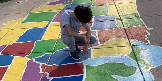 Pastor Edgar Rodriguez's oldest son prays over Illinois in a street painting of a map of the U.S. in the Logan Square neighborhood in Chicago while on a prayer march.