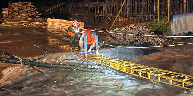 A rescuer helps a worker cross a ladder to get across floodwaters from a construction site in Jing'an county in central China's Jiangxi province midnight Friday, July 3, 2020.