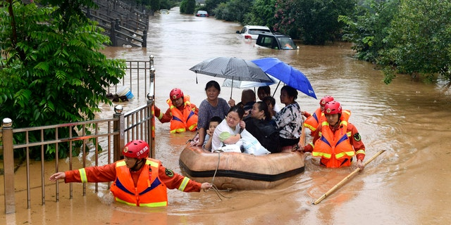 Rescuers evacuate residents on a raft through flood waters in Jiujiang in central China's Jiangxi province July 8.