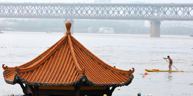 Residents swim past a riverside pavilion submerged by the flooded Yangtze River in Wuhan in central China's Hubei province July 8.