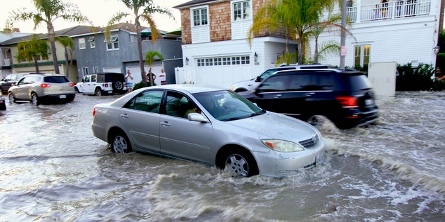 Vehicles drive through flooded streets in Newport Beach, Calif., July 3. The combination of surf and high tides could produce minor coastal flooding at the lowest coastal locations in the evenings during high tide this holiday weekend, according to the National Weather Service.