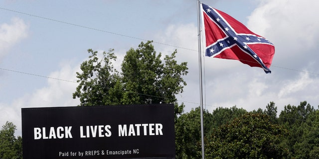 A Black Lives Matter billboard is seen next to a Confederate flag in Pittsboro, N.C., July 16. A group in North Carolina erected the billboard to counter the flag that stands along the road. (AP Photo/Gerry Broome)