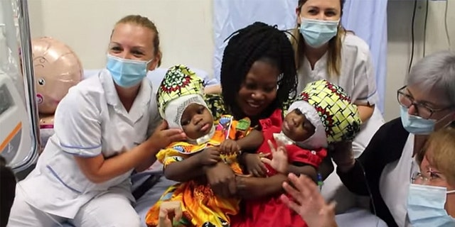 Ermine Nzotto holds her twins, Ervina and Prefina, after surgery. (Photo credit: Bambino Gesu Pediatric Hospital)