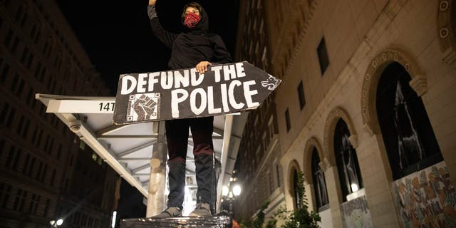 A protester holds a sign calling for the defunding of police at a protest on Saturday, July 25, 2020, in Oakland, Calif. (AP Photo/Christian Monterrosa)