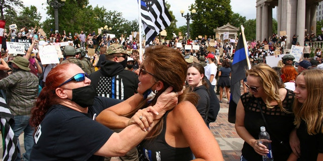 Two women begin to fight at a pro-law enforcement rally that clashed with counter-protesters demonstrating against racial inequality, in Denver, Colorado, U.S. on July 19, 2020. (Reuters/Kevin Mohatt)