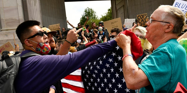 Anti-police protesters, left, clash with a Pro-Police Rally supporter when dueling rallies collided at Civic Center Park on July 19, 2020 in Denver, Colorado. (Photo by Helen H. Richardson/MediaNews Group/The Denver Post via Getty Images)