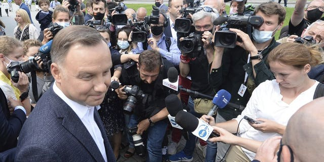 Candidate in Poland's tight presidential election runoff, incumbent President Andrzej Duda talks to reporters after having cast his ballot at a polling station in his hometown of Krakow, Poland, on Sunday, July 12, 2020. Conservative Duda is running against liberal Warsaw Mayor Rafal Trzaskowski and latest opinion polls suggest the race will be decided by a very narrow margin.