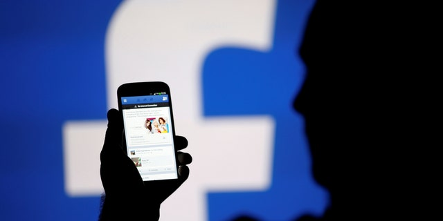 A man is silhouetted against a video screen with a Facebook logo. REUTERS/Dado Ruvic
