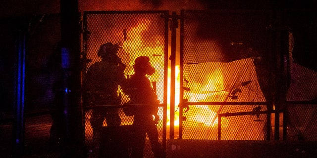 election 2020  Donald Trump  President Trump  Conservative News  RNC Federal officers guard the Mark O. Hatfield U.S. Courthouse as a fire lit by protesters burns on the other side of a perimeter fence  July 25, in Portland, Ore. (AP Photo/Noah Berger)
