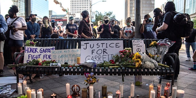 People gather around a makeshift memorial lined with flowers and candles at a vigil for Garrett Foster on July 26, 2020, in downtown Austin, Texas. Foster, 28, who was armed and participating in a Black Lives Matter protest, was shot and killed after a chaotic altercation with a motorist who allegedly drove into the crowd. (Sergio Flores/Getty Images)