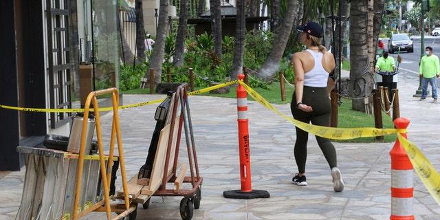 A woman walks past boarded storefronts in the Waikiki neighborhood of Honolulu, Saturday, July 25, 2020, as Hurricane Douglas approaches.