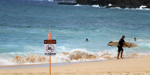 A surfer leaves the water in Honolulu, Saturday, July 25, 2020, as Hurricane Douglas approaches.