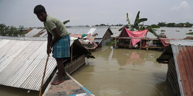 A man rows a boat near his submerged house in Gagolmari village, in Morigaon district of Assam, India, July 14.